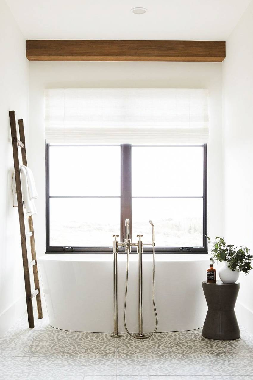 If storage space is limited in your bathroom, consider leaning a stylish ladder against the wall and bringing in a stool for decorative objects and shower products