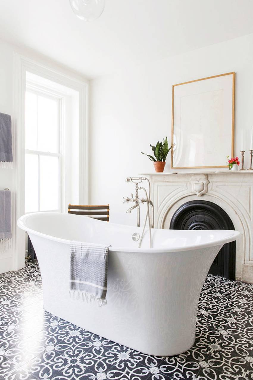 The Mediterranean floor tiles ground the sleek freestanding tub and traditional fireplace for a nice balance between formal and casual